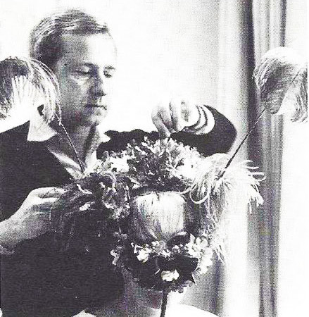 Originally a Milliner, Adolfo was formed his fantasy creations. He is shown adding the finishing touches to a 1965 confection of violets and feathers.